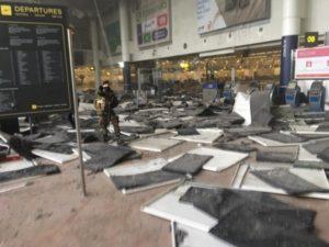 Policial permanece de guarda na área de embarque do Aeroporto Internacional de Zaventem, em Bruxelas, na Bélgica, onde duas bombas foram detonadas – Foto: The Int'l Spectator/Reprodução